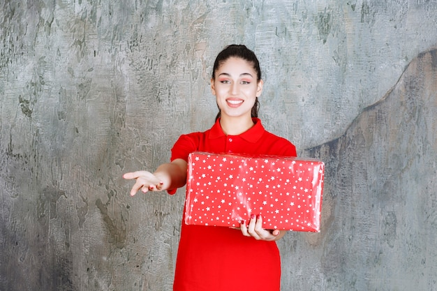 Teenager girl holding a red gift box with white dots on it and inviting someone next to her.