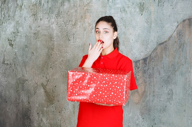 Teenager girl holding a red gift box with white dots on it and looks scared and terrified