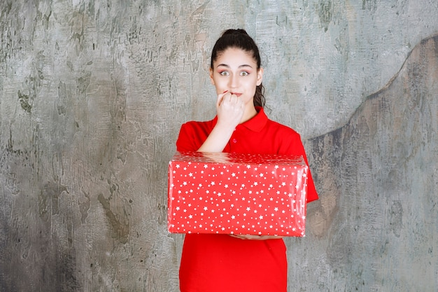 Teenager girl holding a red gift box with white dots on it and looks scared and terrified.