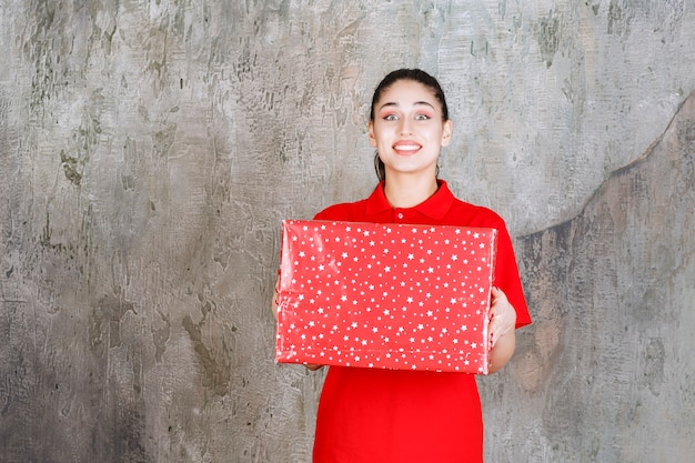 Teenager girl holding a red gift box with white dots on it.