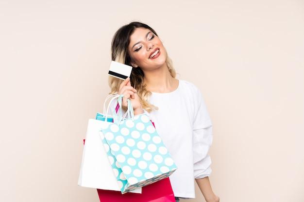 Девушка-подросток держит хозяйственные сумки и кредитную карту