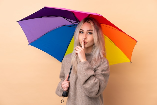 Teenager girl holding an umbrella over wall doing silence gesture