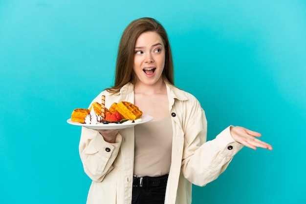 Teenager girl holding waffles over isolated blue background with surprise expression while looking side