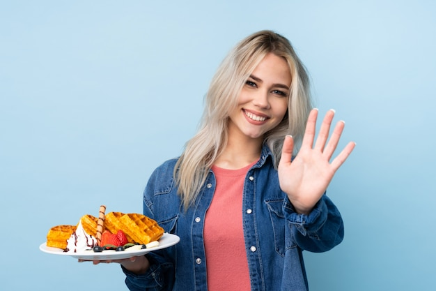 Teenager girl holding waffles over isolated blue wall saluting with hand with happy expression