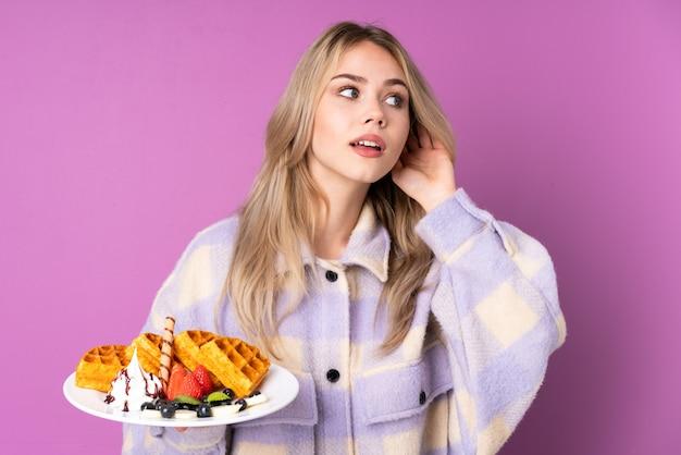 Девушка-подросток держит вафли, изолированные на фиолетовом, слушая что-то, положив руку на ухо