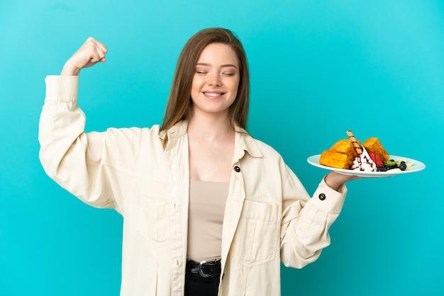 Девушка-подросток держит вафли на синем фоне и делает сильный жест