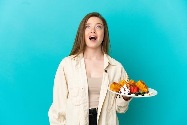 Девушка-подросток держит вафли на синем фоне, глядя вверх и с удивленным выражением лица