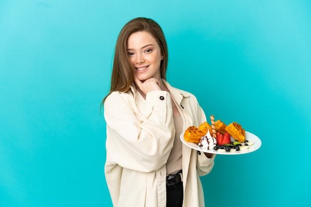 Девушка-подросток держит вафли на синем фоне, думая об идее, глядя вверх
