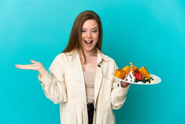Девушка-подросток держит вафли на синем фоне с шокированным выражением лица