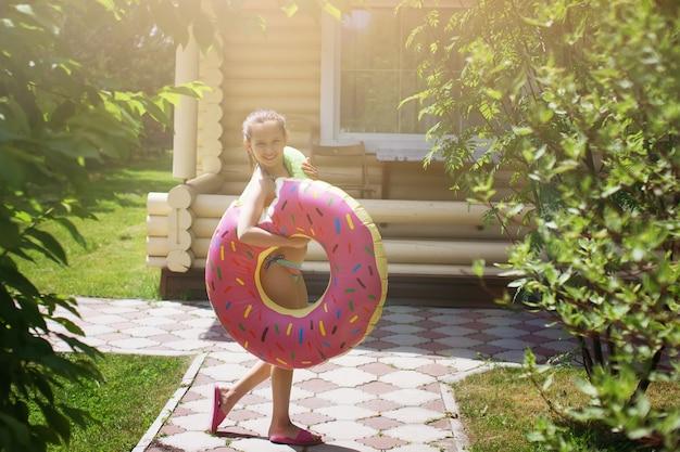 インフレータブルプールリング付きの水着を着た10代の少女は、木々や草の間の石の小道を歩きます。