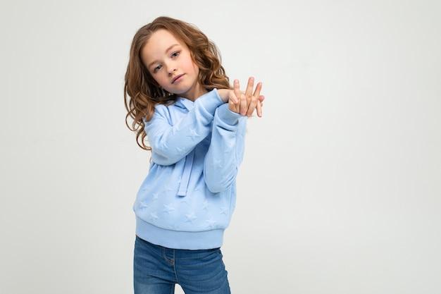 青いパーカーのポーズでティーンエイジャーの女の子