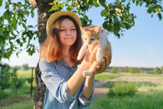 Девушка-подросток в шляпе из джинсового платья держит в руках маленького рыжего котенка, деревенский стиль