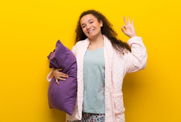 指でokサインを示すパジャマでティーンエイジャーの女の子