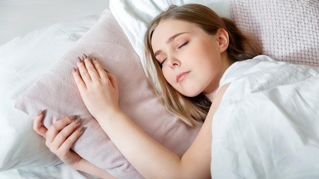 잠 옷에있는 십 대 소녀는 아침 시간에 침실에서 잔 다. 침대에서 자 고하는 젊은 여자. 금발 십 대 소녀의 초상화는 흰색 분홍색 베개에 건강한 ..