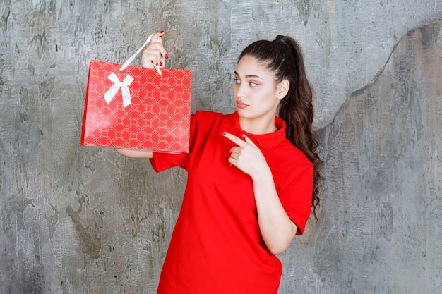 赤い買い物袋を持って赤いシャツを着たティーンエイジャーの女の子は、混乱して思慮深く見えます。