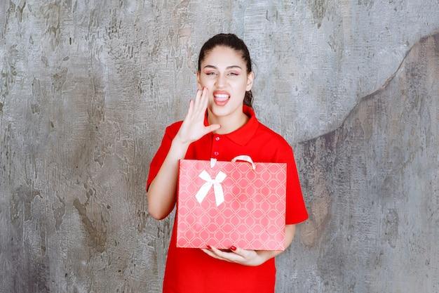 Девушка-подросток в красной рубашке держит красную сумку для покупок и громко кричит