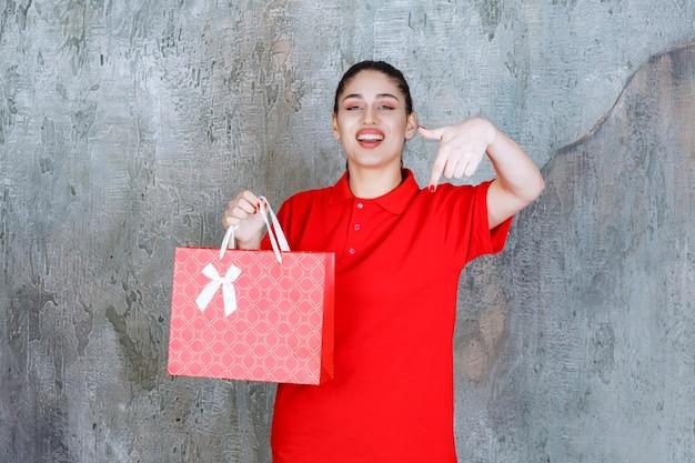 Девушка-подросток в красной рубашке держит красную хозяйственную сумку и улыбается с удивлением.
