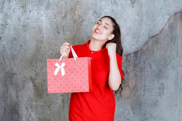 Девушка-подросток в красной рубашке держит красную хозяйственную сумку.