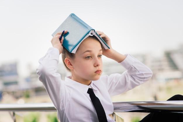 放課後や大学の授業、手にノートを休んで都市公園で夏のティーンエイジャーの女の子。