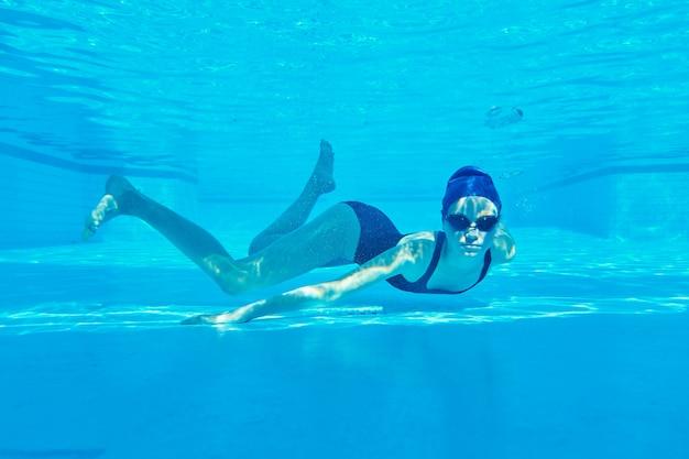 ゴーグルと水泳帽のプールで水中水泳で10代の女の子