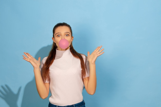 Девушка-подросток надувает пузырь жевательной резинки