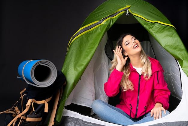 Девушка-подросток в зеленой палатке кемпинга
