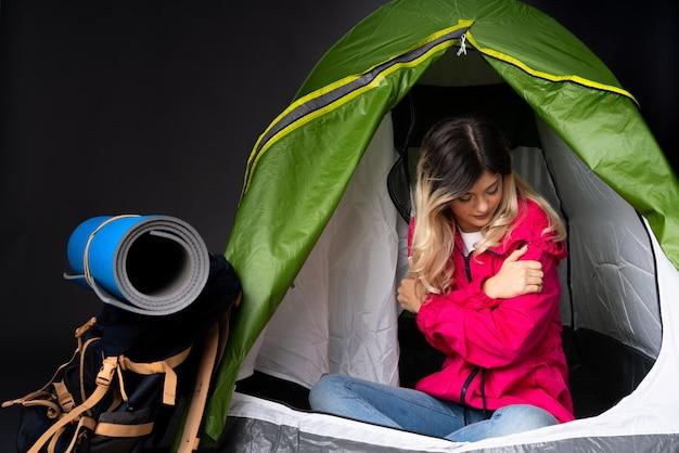 녹색 캠핑 텐트 안에 십 대 소녀
