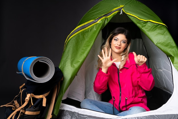 キャンプの緑のテントの中のティーンエイジャーの女の子