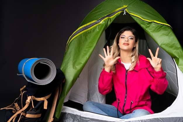 Teenager girl inside a camping green tent isolated on black background counting eight with fingers