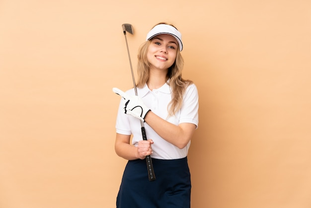 Teenager girl isolated on beige wall playing golf and pointing to the lateral