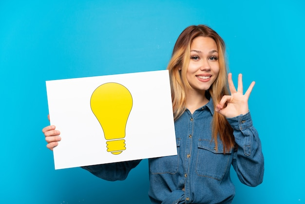 Teenager girl over isolated blue background holding a placard with bulb icon with ok sign