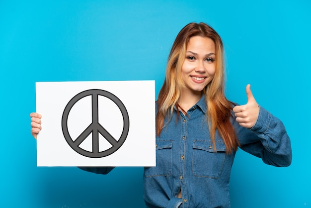 Teenager girl over isolated blue background holding a placard with peace symbol with thumb up