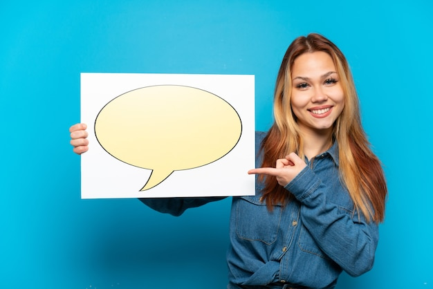 Teenager girl over isolated blue background holding a placard with speech bubble icon and pointing it