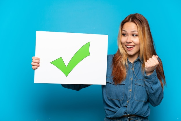 Teenager girl over isolated blue background holding a placard with text green check mark icon and celebration a victory