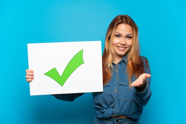 Teenager girl over isolated blue background holding a placard with text green check mark icon making a deal