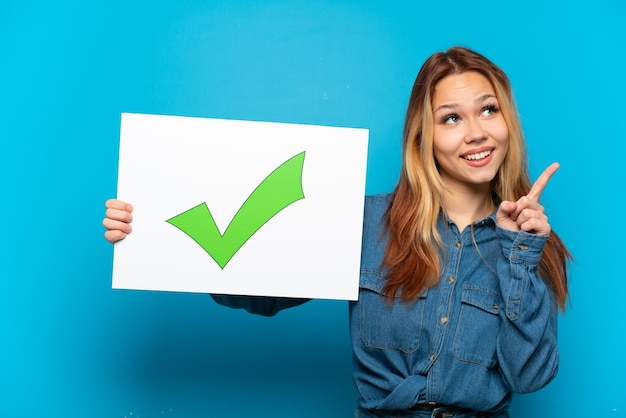 Teenager girl over isolated blue background holding a placard with text green check mark icon and thinking