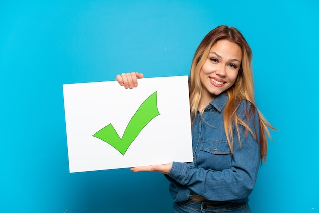 Teenager girl over isolated blue background holding a placard with text green check mark icon with happy expression