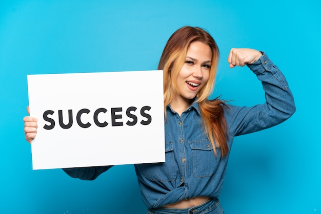 Teenager girl over isolated blue background holding a placard with text success and doing strong gesture
