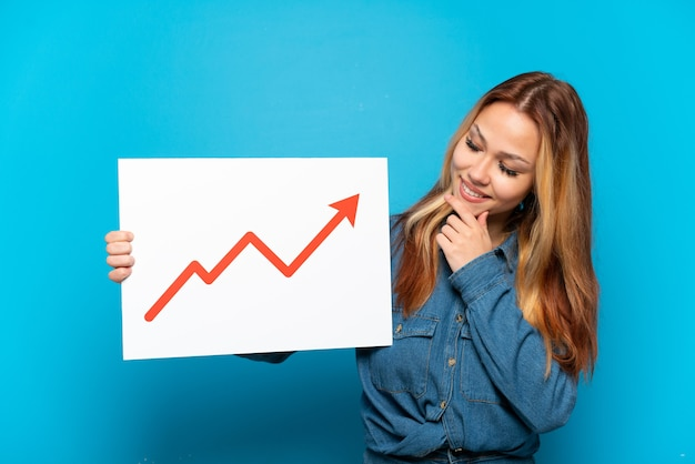 Teenager girl over isolated blue background holding a sign with a growing statistics arrow symbol and thinking
