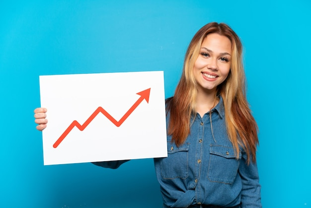 Teenager girl over isolated blue background holding a sign with a growing statistics arrow symbol with happy expression