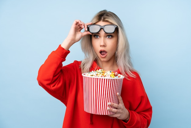 Teenager girl over isolated blue wall surprised with 3d glasses and holding a big bucket of popcorns