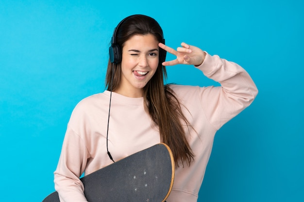 Teenager girl over isolated blue wall with a skate with happy expression