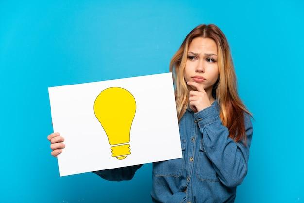 電球のアイコンが付いたプラカードを持って、考えて分離された 10 代の少女