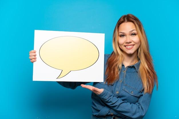 Девушка-подросток изолирована, держа плакат со значком пузыря речи
