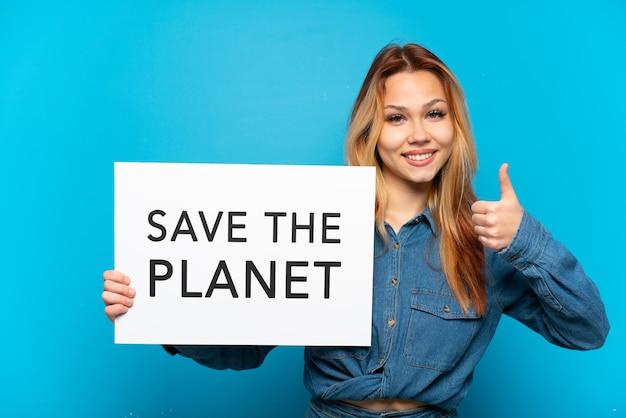 Девушка-подросток изолирована, держа плакат с текстом «спасите планету» с большим пальцем вверх
