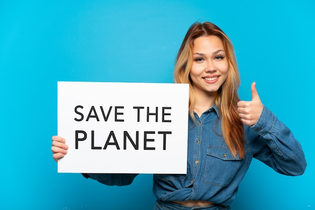 Teenager girl isolated holding a placard with text save the planet with thumb up