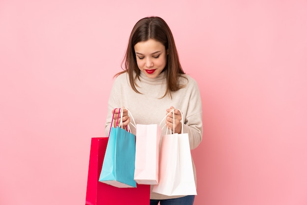 십 대 소녀 쇼핑 가방을 들고 안에 찾고 분홍색 벽에 고립