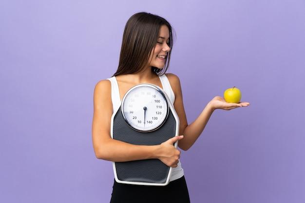 Девушка-подросток изолирована на фиолетовом, держа весы, глядя на яблоко