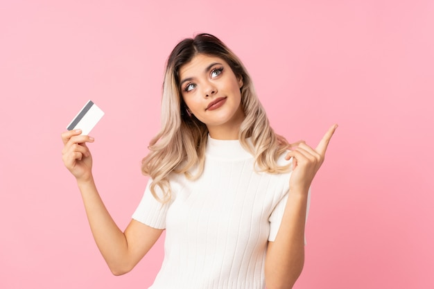 Teenager girl over isolated pink background holding a credit card