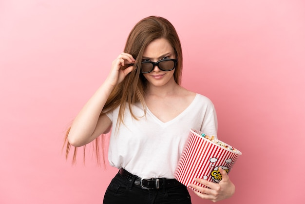 Teenager girl over isolated pink background surprised with 3d glasses and holding a big bucket of popcorns